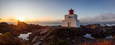 Beautiful Panoramic View of the Lighthouse on the Rocky Pacific Ocean Coast during a colorful cloudy sunrise. Taken on Wild Pacific Trail in Ucluelet, Vancouver Island, BC, Canada.