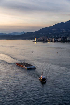 West Vancouver, British Columbia, Canada. Aerial View of a Tugboat in a modern cityscape on the Pacific Ocean Coast during an Autumn sunny and cloudy sunset.