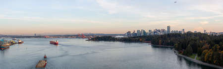 Downtown Vancouver, British Columbia, Canada. Aerial Panoramic View of a modern cityscape on the Pacific Ocean Coast during an Autumn sunny and cloudy sunset. Stock Photo