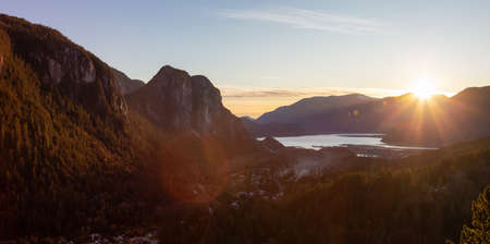 Squamish, North of Vancouver, British Columbia, Canada. Beautiful Aerial Panoramic View from the top of the Mountain of a small town surrounded by Canadian Nature during Autumn Sunset.