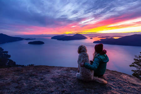 Adventurous Girl Hiking on top of a Mountain with a dog during a colorful sunset. Taken on Tunnel Bluffs Hike, near Vancouver and Squamish, British Columbia, Canada. Stok Fotoğraf