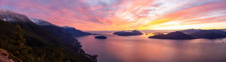 Tunnel Bluffs Hike, in Howe Sound, North of Vancouver, British Columbia, Canada. Panoramic Canadian Mountain Landscape View from the Peak during sunny winter sunset.