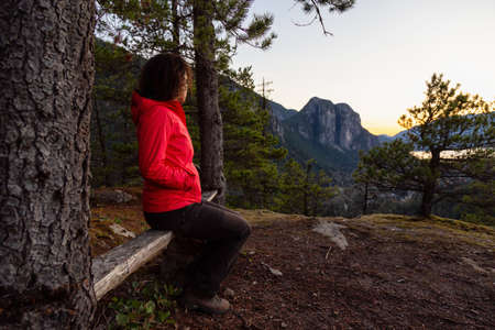 Adventurous Girl relaxing on a bench in the mountains during a sunny Autumn Sunset. Taken Squamish, North of Vancouver, British Columbia, Canada. Concept: Adventure, freedom, lifestyle