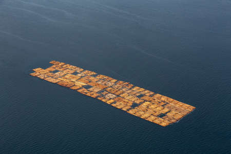Aerial View of Tugboat towing Lumber in the ocean during a hazy summer day. Taken in Sunshine Coast, BC, Canada. Stock Photo