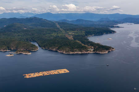 Aerial View of Tugboat towing Lumber in the ocean with mountain landscape in the background during a hazy summer day. Taken in Sunshine Coast, BC, Canada. Stock Photo