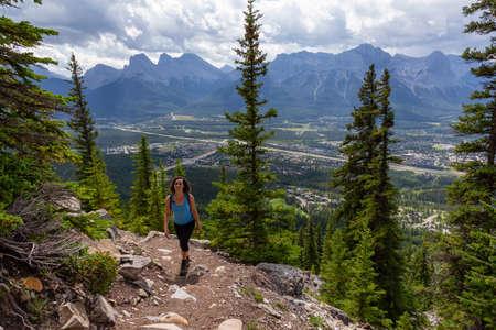 Abenteuerliches Mädchen wandert an einem bewölkten und regnerischen Tag einen felsigen Berg hinauf. Aufgenommen von Mt Lady MacDonald, Canmore, Alberta, Kanada.