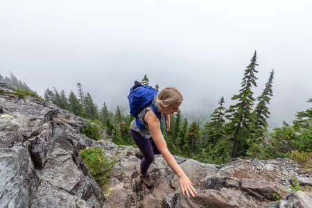 Adventurous Girl is hiking in beautiful green woods in the mountains during a cloudy summer morning. Taken on Crown Mountain, North Vancouver, BC, Canada.