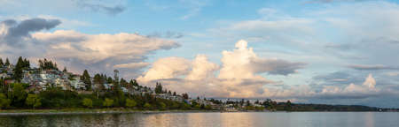 White Rock, British Columbia, Canada. Beautiful Panoramic View of Residential Homes on the Ocean Shore during a sunny and cloudy summer sunset.