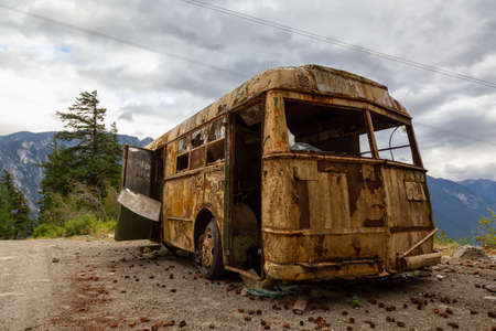 Old, Rusty, Broken and Abandoned Bus on a Dirt Road in the Mountain Valley near a lake during a cloudy summer evening. Taken on Anderson Lake Rd, near Lillooet, BC, Canada.