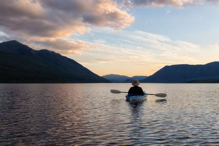 Adventurous Man Kayaking in Lake McDonald during a sunny summer sunset with American Rocky Mountains in the background. Taken in Glacier National Park, Montana, USA.