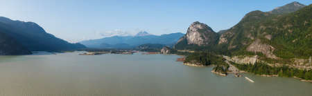 Aerial panoramic view of Sea to Sky Highway with Chief Mountain in the background during a sunny summer day. Taken near Squamish, North of Vancouver, British Columbia, Canada.