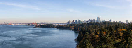 Downtown Vancouver, British Columbia, Canada. Beautiful Aerial Panoramic View of Seawall in Stanley Park with Downtown City in Background during a sunny Autumn Evening.