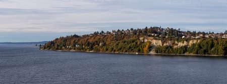 Beautiful Panoramic Aerial View of Residential Homes on the Ocean Shore during a cloudy autumn evening. Taken in Smith Cove Park, Seattle, Washington, United States.