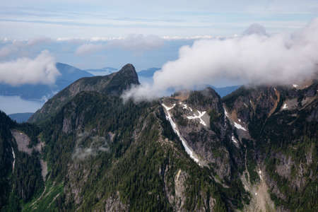 Aerial Landscape View of the Howe Sound Mountains during a cloudy summer morning. Taken North of Vancouver, British Columbia, Canada.