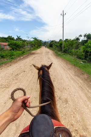 Horseback Riding on a dirty trail in the country side near a small Cuban Town during a vibrant sunny day. Taken in Trinidad, Cuba. 版權商用圖片