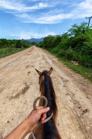 Horseback Riding on a dirty trail in the country side near a small Cuban Town during a vibrant sunny day. Taken in Trinidad, Cuba. Archivio Fotografico