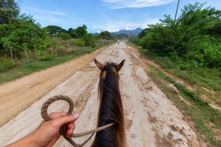 Horseback Riding on a dirty trail in the country side near a small Cuban Town during a vibrant sunny day. Taken in Trinidad, Cuba. Banco de Imagens