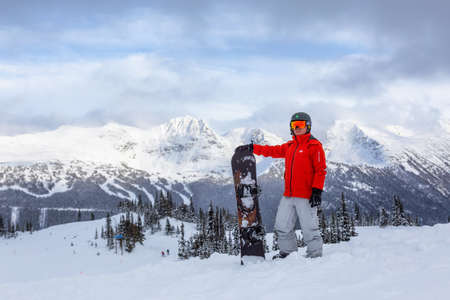 Whistler, British Columbia, Canada - December26, 2019: Male Snowboarder is riding down a ski run in wintertime.