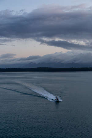 Aerial View of a Boat riding in the American Mountain Landscape on the Ocean Coast during a cloudy and rainy sunrise in fall season. Taken in Glacier Bay National Park and Preserve, Alaska, USA. 版權商用圖片