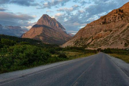 Schöne Aussicht auf eine malerische Straße in der amerikanischen Rocky Mountain-Landschaft bei einem bewölkten Morgensonnenaufgang. Aufgenommen im Glacier National Park, Montana, USA.