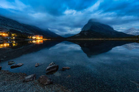 Beautiful View of the reflection in the water with the Cloudy Morning Sunrise in the American Rockies. Taken in Swiftcurrent Lake, Glacier National Park, Montana, United States.