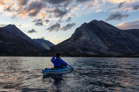 Adventurous Man Kayaking in Glacier Lake surrounded by the beautiful Canadian Rocky Mountains during a cloudy summer sunset. Taken in Upper Waterton Lake, Alberta, Canada. 版權商用圖片