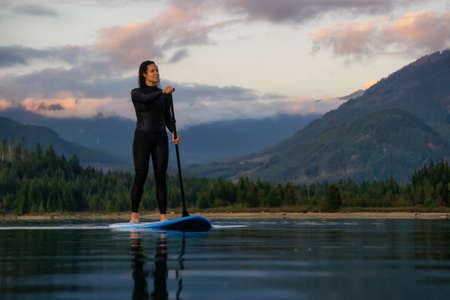 Adventurous Girl on a Paddle Board is paddling in a calm lake with mountains in the background during a colorful summer sunset. Taken in Stave Lake near Vancouver, BC, Canada. 版權商用圖片