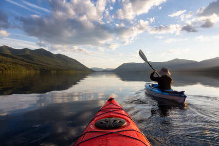 Adventurous Man Kayaking in Lake McDonald during a sunny summer evening with American Rocky Mountains in the background. Taken in Glacier National Park, Montana, USA.