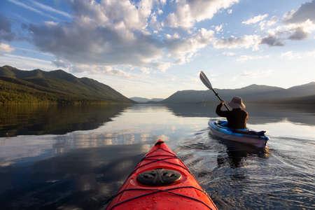 Uomo avventuroso in kayak nel lago McDonald durante una soleggiata serata estiva con montagne rocciose americane sullo sfondo. Preso nel Parco Nazionale di Glacier, Montana, USA.