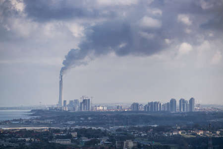 Aerial View of an Industrial Site emitting dark cloud of smoke into the air. Taken in Netanya, Center District, Israel.