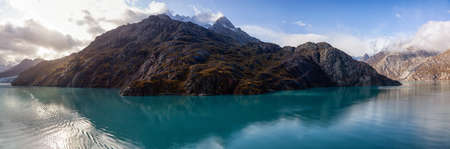 Beautiful Panoramic View of American Mountain Landscape on the Ocean Coast during a cloudy and colorful morning in fall season. Taken in Glacier Bay National Park and Preserve, Alaska, USA. Stockfoto