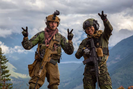 Chilliwack, British Columbia, Canada - October 5, 2019: Army Man wearing Tactical Uniform and holding Machine gun in the Outdoor Mountains showing peace signs.