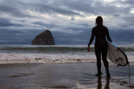 Adventurous Girl with a Surf Board is going surfing in the Ocean during a cloudy summer sunset. Taken in Pacific City, Oregon Coast, United States of America. 版權商用圖片