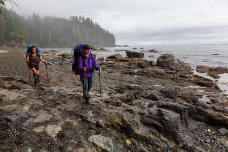 Adventurous girl hiking Juan de Fuca Trail to Sombrio Beach on the Pacific Ocean Coast during a misty summer day. Taken near Port Renfrew, Vancouver Island, BC, Canada. Foto de archivo