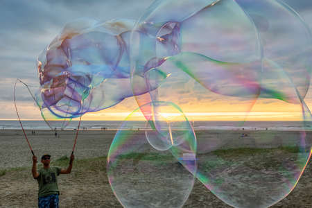 Seaside, Oregon, USA - September 6, 2019: Man making big Soap Bubbles on the sandy beach during a dramatic summer sunset.