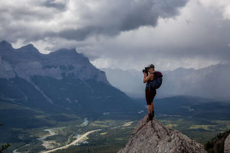 Adventurous Girl taking pictures on top of a rocky mountain during a cloudy and rainy day. Taken from Mt Lady MacDonald, Canmore, Alberta, Canada. Foto de archivo