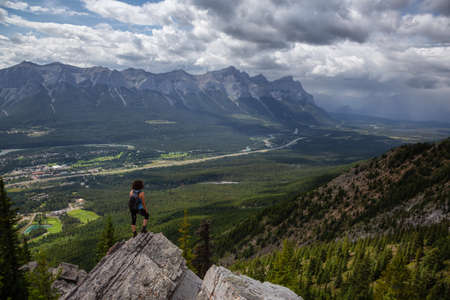 Adventurous Girl is hiking up a rocky mountain during a cloudy and rainy day. Taken from Mt Lady MacDonald, Canmore, Alberta, Canada. Foto de archivo