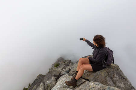Young Adventurous Girl on top of a rugged rocky mountain taking a selfie during a cloudy summer morning. Taken on Crown Mountain, North Vancouver, BC, Canada. Stock Photo
