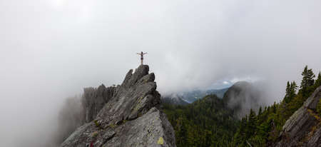 Adventurous Girl with Open Arms on top of a rugged rocky mountain during a cloudy summer morning. Taken on Crown Mountain, North Vancouver, BC, Canada. 版權商用圖片