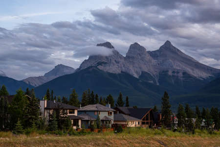 Beautiful view of Residential Homes with Canadian Rocky Mountains in the background during a cloudy summer sunset. Taken in Canmore, Alberta, Canada. Banco de Imagens
