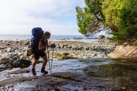 Chica aventurera senderismo Juan de Fuca Trail a Bear Beach en la costa del Océano Pacífico durante una soleada y brumosa mañana de verano. Tomada cerca de Port Renfrew, Isla de Vancouver, BC, Canadá.