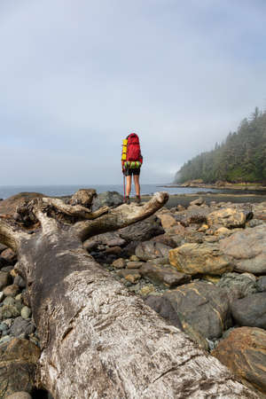 Adventurous girl hiking Juan de Fuca Trail to Bear Beach on the Pacific Ocean Coast during a sunny and foggy summer morning. Taken near Port Renfrew, Vancouver Island, BC, Canada.