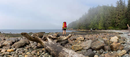 Adventurous girl hiking Juan de Fuca Trail to Bear Beach on the Pacific Ocean Coast during a sunny and foggy summer morning. Taken near Port Renfrew, Vancouver Island, BC, Canada. Foto de archivo