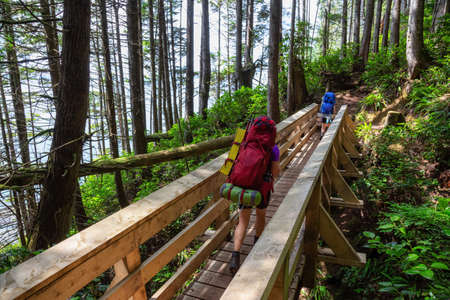 Adventurous female is hiking Juan de Fuca Trail near Mystic Beach on the Pacific Ocean Coast during a sunny summer day. Taken near Port Renfrew, Vancouver Island, BC, Canada. Foto de archivo