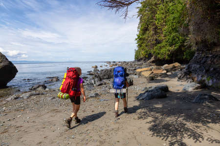 Adventurous friends are hiking Juan de Fuca Trail to Mystic Beach on the Pacific Ocean Coast during a sunny summer day. Taken near Port Renfrew, Vancouver Island, BC, Canada. Foto de archivo
