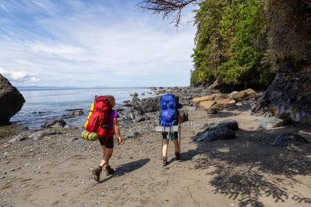 Amigos aventureros están caminando por el sendero Juan de Fuca hasta Mystic Beach en la costa del Océano Pacífico durante un día soleado de verano. Tomada cerca de Port Renfrew, Isla de Vancouver, BC, Canadá.