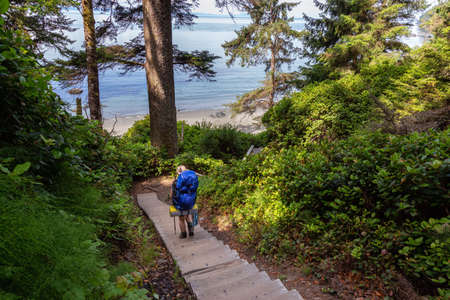 Adventurous female is hiking Juan de Fuca Trail to Mystic Beach on the Pacific Ocean Coast during a sunny summer day. Taken near Port Renfrew, Vancouver Island, BC, Canada. Foto de archivo