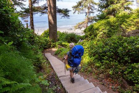 Mujer aventurera camina por el sendero Juan de Fuca hasta Mystic Beach en la costa del Océano Pacífico durante un día soleado de verano. Tomada cerca de Port Renfrew, Isla de Vancouver, BC, Canadá.