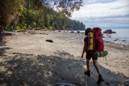 Adventurous girl is hiking Juan de Fuca Trail to Mystic Beach on the Pacific Ocean Coast during a sunny summer day. Taken near Port Renfrew, Vancouver Island, BC, Canada.