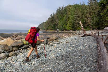 Chica aventurera senderismo Juan de Fuca Trail a Bear Beach en la costa del Océano Pacífico durante una soleada y brumosa mañana de verano. Tomada cerca de Port Renfrew, Isla de Vancouver, BC, Canadá. Foto de archivo